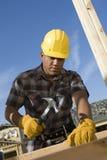 Trabalhador que martela o prego na prancha Fotografia de Stock Royalty Free