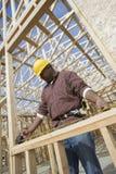 Trabalhador que mede o feixe de madeira Imagem de Stock Royalty Free
