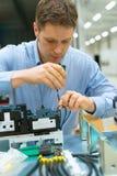 Trabalhador que monta componentes eletrônicos Foto de Stock Royalty Free