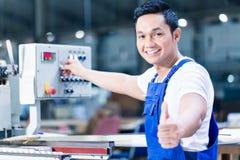 Trabalhador que mostra os polegares acima na planta de produção asiática foto de stock