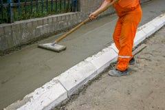 Trabalhador que nivela o concreto fresco  Fotos de Stock Royalty Free