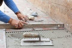Trabalhador que nivela o pavimento novo com uma ferramenta específica Fotografia de Stock Royalty Free