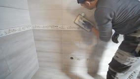 Trabalhador que põe a fuga sobre a parede na cozinha Reboco da telha filme