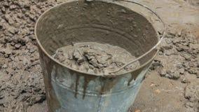 Trabalhador que põe o concreto na cubeta video estoque