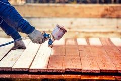 Trabalhador que pinta a madeira marrom, renovando a cerca de madeira exterior Trabalhador que usa a arma de pulverizador foto de stock royalty free