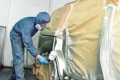 Trabalhador que pinta um carro. fotos de stock