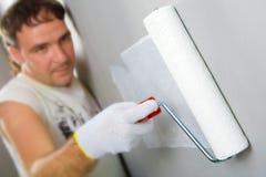 Trabalhador que pinta um rolo do whith da parede Imagem de Stock