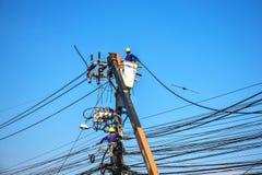Trabalhador que repara o trabalho no polo de poder bonde do cargo Foto de Stock