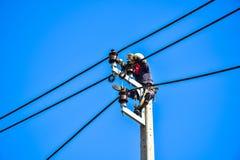 Trabalhador que repara o trabalho no polo de poder bonde do cargo Imagem de Stock