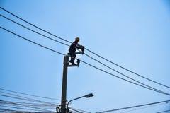 Trabalhador que repara o trabalho no polo de poder bonde do cargo Imagem de Stock Royalty Free