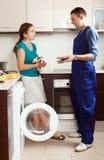 Trabalhador que repara uma máquina de lavar para a mulher Imagem de Stock Royalty Free