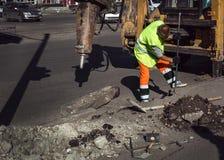 Trabalhador que repara uma pé de cabra do martelo da estrada Imagem de Stock Royalty Free