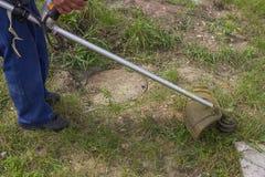 Trabalhador que sega a grama com o ajustador da corda do gás Fotos de Stock