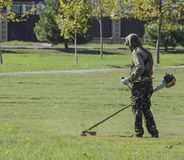 Trabalhador que sega o gramado Ajustador de sega da grama Fotografia de Stock Royalty Free