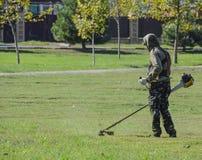 Trabalhador que sega o gramado Ajustador de sega da grama Foto de Stock Royalty Free