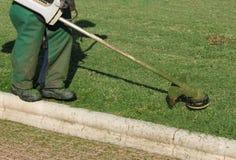 Trabalhador que sega os gramados imagem de stock
