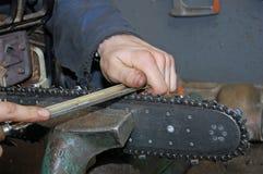 Trabalhador que sharpening a serra de cadeia Fotos de Stock Royalty Free