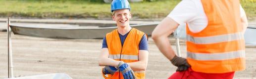 Trabalhador que sorri a um amigo fotografia de stock