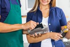 Trabalhador que Swiping o cartão de crédito com terra arrendada da mulher Fotos de Stock