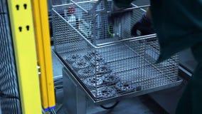Trabalhador que toma as peças terminadas fora da cadeia de fabricação na fábrica Peças da máquina video estoque