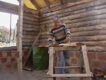 Trabalhador que trabalha em uma maneira do artesão na construção de uma cabana rústica de madeira imagem de stock