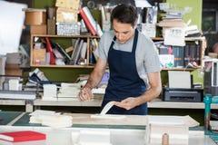 Trabalhador que trabalha na tabela na indústria de papel Imagens de Stock