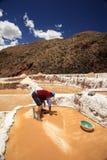 Trabalhador que trabalha nos pântanos de sal de Cusco no Peru Imagens de Stock