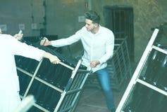 Trabalhador que transporta garrafas do vinho na indústria de vinho espumante Fotografia de Stock
