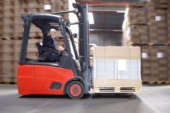 Trabalhador que transporta o estoque na empilhadeira Foto de Stock