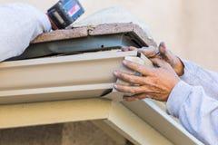 Trabalhador que une a calha de alumínio da chuva à fáscia da casa fotografia de stock