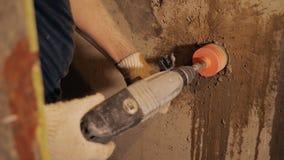 Trabalhador que usa a broca de martelo no local video estoque
