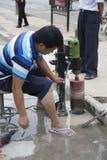 Trabalhador que usa a broca na estrada Fotos de Stock Royalty Free
