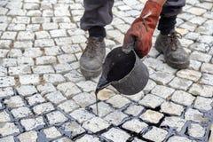 Trabalhador que usa a cubeta do alcatrão ou do passo, alcatrão líquido de espalhamento Fotografia de Stock Royalty Free