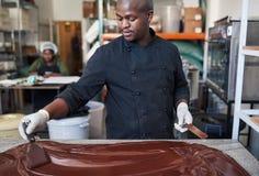 Trabalhador que usa espátulas para misturar o chocolate em uma tabela fotografia de stock royalty free