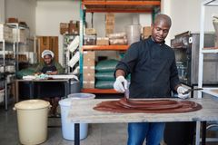 Trabalhador que usa espátulas para misturar o chocolate em uma tabela da fábrica foto de stock