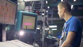 Trabalhador que usa o écran sensível que opera a máquina industrial video estoque