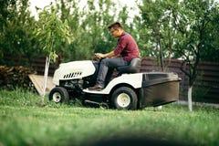 Trabalhador que usa o ajustador profissional da grama, cortador de grama Fotos de Stock Royalty Free