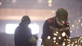 Trabalhador que usa o moedor industrial nas peças de metal no armazém industrial da oficina vídeos de arquivo