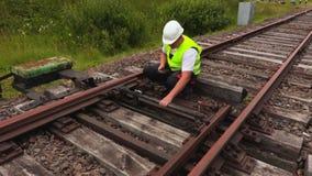 Trabalhador que usa o PC da tabuleta na trilha railway filme