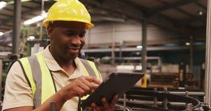 Trabalhador que usa a tabuleta digital na fábrica da garrafa filme