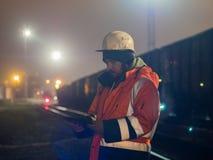 Trabalhador que usa a tabuleta moderna no hignt Está no capacete e no revestimento reflexivo Imagens de Stock