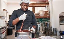 Trabalhador que usa um marie do bain para misturar o chocolate de derretimento imagem de stock royalty free