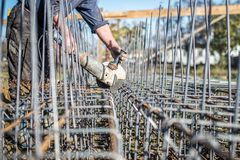 Trabalhador que usa um moedor de ângulo para cortar as barras de aço usadas para o reforço Fotos de Stock