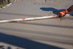 Trabalhador que usa uma espátula de madeira para o cimento após ter derramado concreto pronto-misturado fotos de stock