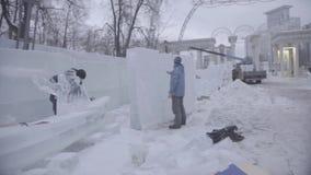 Trabalhador que usa uma serra de cadeia que cinzela uma escultura de gelo Os homens discutem o trabalho com as esculturas de gelo filme
