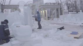 Trabalhador que usa uma serra de cadeia que cinzela uma escultura de gelo Os homens discutem o trabalho com as esculturas de gelo vídeos de arquivo