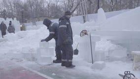 Trabalhador que usa uma serra de cadeia que cinzela uma escultura de gelo Os homens discutem o trabalho com as esculturas de gelo video estoque