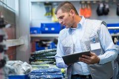 Trabalhador que verifica os níveis conservados em estoque na sala de loja fotografia de stock royalty free