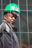 Trabalhador que veste um capacete verde e que olha a câmera Foto de Stock