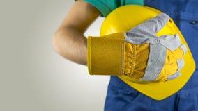 Trabalhador que veste uma luva que guarda um capacete de segurança Fotografia de Stock Royalty Free